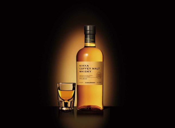 Bottle of Nikka whisky next to shot glass with dramatic lighting