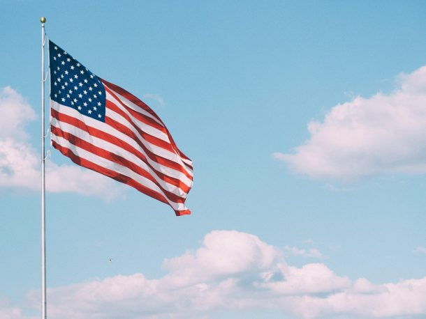 An American flag waves high in a blue sky, with a few clouds.