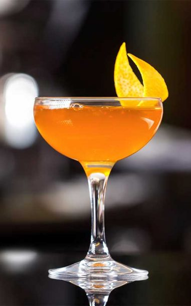 Red-orange sidecar cocktail in coupe glass with orange peel garnish