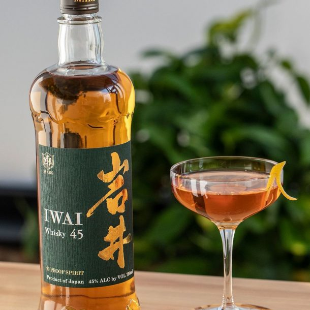 Bottlle of Iawai next to coupe glass cocktail