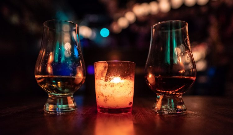 Two whisky glasses in a dark-lit bar with a candle between them.
